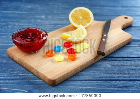 Cough drops with jam and lemon on cutting board
