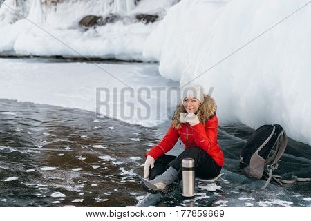 The tourist girl decided to stop to rest and drink tea from the thermos. The traveler made a halt right on the ice near the rocky shore. The backpack is removed. The tea is very hot. Live shooting.