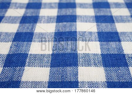 Blue and white checkered fabric as a background texture with selected focus