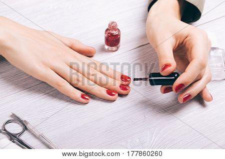 Close-up Of A Woman Painting Her Nails With Red Lacquer