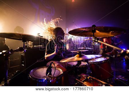 The drummer sits at the drums at the rock concert. The crowd to the club