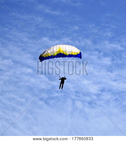 Single man enjoying freedom of paragliding on the blue sky