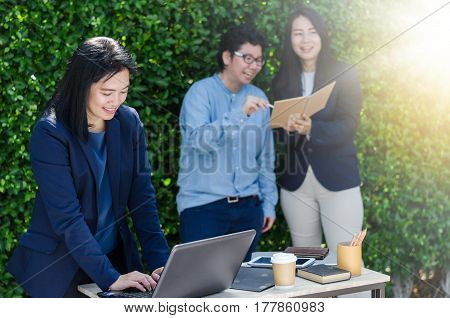 Asian Business Woman Using Computer Laptop And Her Team Dicussing Something While Working.