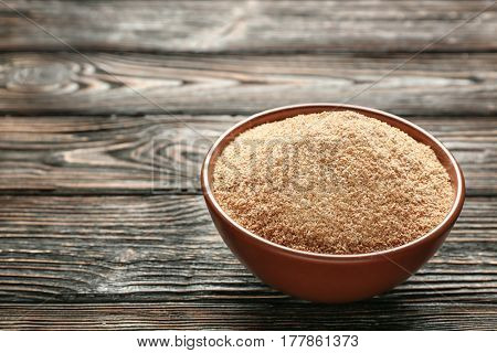 Bowl with bread crumbs on wooden table