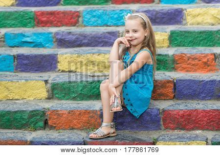 Small Smiling Baby Girl In Blue Dress On Colorful Stairs