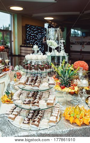 Chocolate choux pastries on glass stand on the wedding candybar. different fruits