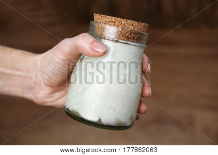 Female hand holding jar with coconut oil on blurred background
