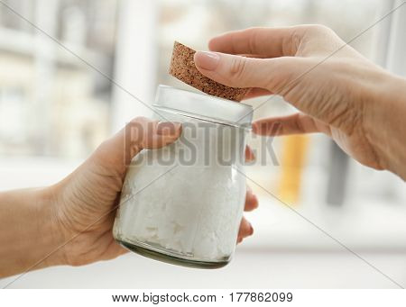 Female hands holding jar with coconut oil on blurred background