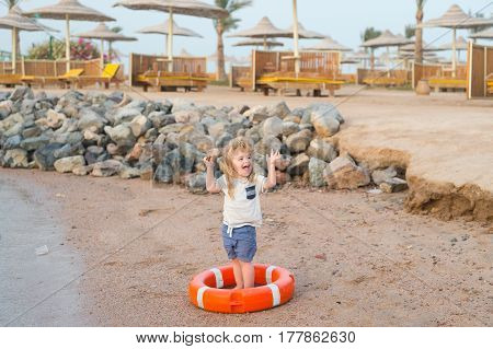 small baby boy or cute child with happy face and blonde hair in shirt and shorts barefoot playing with red safety belt or lifebelt at sandy beach with stones umbrellas on natural background