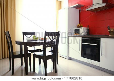 Modern interior of kitchen room with large shiny window and wooden round table