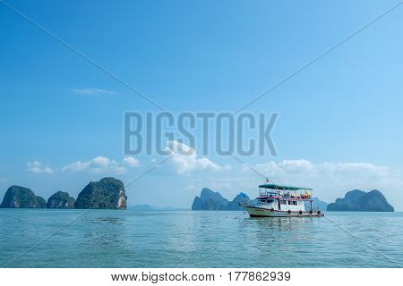 PHANG NGA BAY, THAILAND - MARCH 3, 2017:  Tour boat cruising among the scenic limestone islands in Phang Nga Bay. This is one of Thailands most iconic tourist destinations.