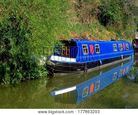 Blue houseboat with its reflection in the canal