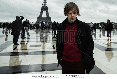 A guy in a red pullover standing against the background of the Eiffel Tower. Young guy