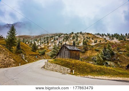 Wooden shed on the bend in the road. Dolomites in Northern Italy. First snow on the pass Giau