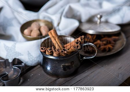 Cinnamon sticks, nutmeg and anise stars in cups over dark scorched wooden background, selective focus, horizontal composition