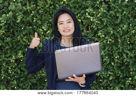 Business success concept. Smiling asian woman holding laptop and showing thumbs up front of green leaf wall background.