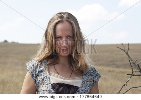 beautiful girl in rustic clothes outdoors in the desert among thorns and dead trees