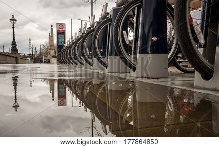 LONDON UK - 8 MARCH 2017: A row of Santander bicycles docked in their station on a grey and wet London day. The bike sharing scheme allows locals and tourists a means of travelling around the UK capital.