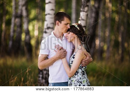 Romance in forest. Beautiful girl with dark hair and brown eyes with a wreath on head in summer dress hugging a man in awhite shirt on a green background. Loving couple in the forest on a sunny day. To love each other. Romance in nature.
