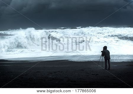 Photographer on black sand beach facing the rough sea natural madness beautiful but dangerous