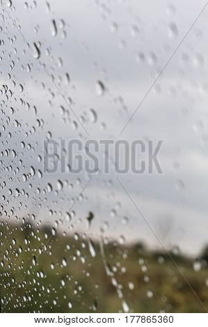 Natural Water Drops On Window Glass With Nature Background.