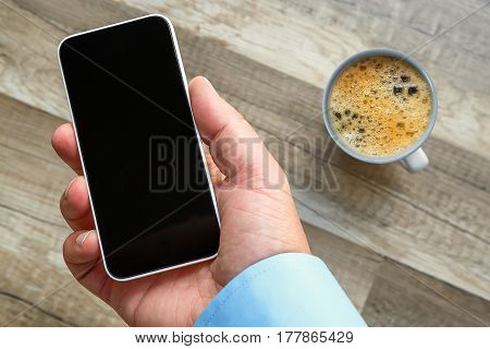Smartphone In Hand At Work With A Blank Area To Insert A Custom Image. Cup Of Tea And Wooden Floor O