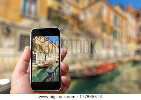 Man Taking A Picture Of A Venice Canal With His Smartphone In Hand