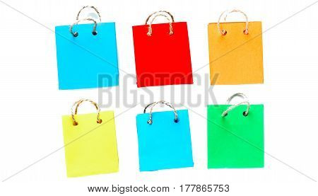 Six colorful tiny shopping bags of paper with rope handles. Isolated over white