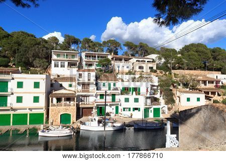Cala Figuera, Spain - November 8, 2016: Men sitting in fishing village port, boats and Mediterranean Sea, Majorca. Cala Figuera encompasses a small traditional fishing community of 577 permanent residences which rises during the tourist season.