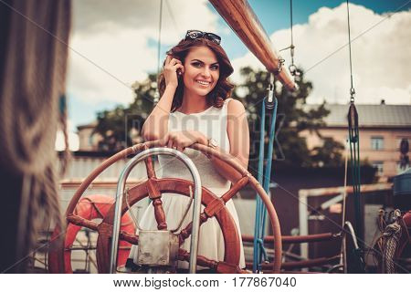 Stylish wealthy woman on a luxury wooden regatta.