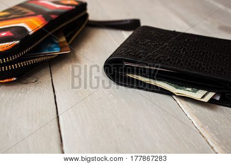 men's and women's wallet with money on wooden background