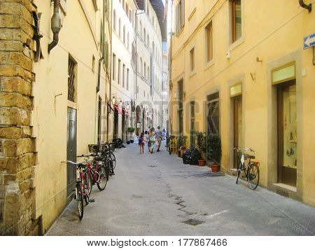 Small local old town street in Tuscany city of Florence, italy, Europe. Architecture colorfull landmark of Florence. Cozy, cute empty cityscape street with parked bikes on bright warm summer day