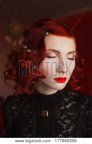 A woman with red curly hair in a black dress and retro makeup on a red background. Red-haired girl with pale skin blue eyes a bright unusual appearance red lips. Noir woman