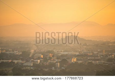 Aerial view of city with layers of mountain range in the morning beautiful cityscape background in warm tone