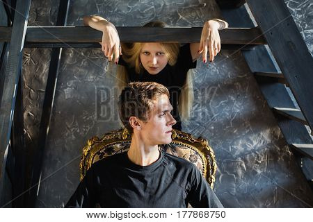 A young man and young blonde woman with long hair. Problem and difficulties in relations. Difficult situation in life. Conceptual photography with problem in family. Actor play. Hard shadows. Show feelings. Hide feelings.