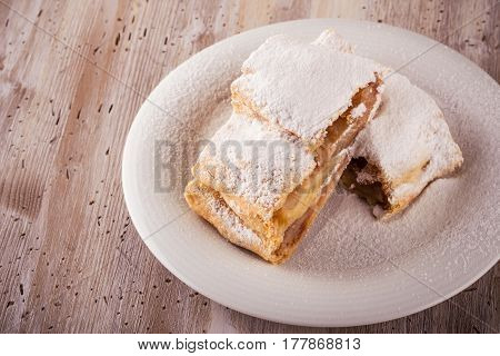 Two Slices Of Apple Strudel With Powder Sugar On White Saucer