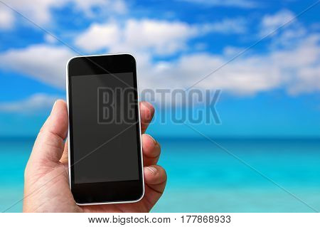 Smartphone In Hand With A Blank Area To Insert A Custom Image. Paradisiac Sea On Background