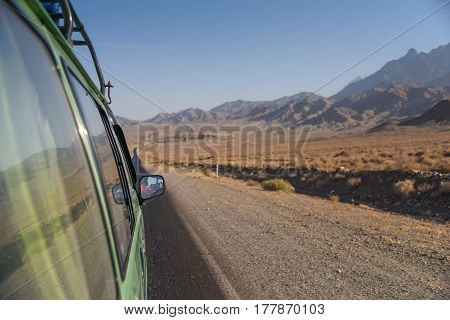 Green van on the road among scenic mountain and stone desert landscape in Iran
