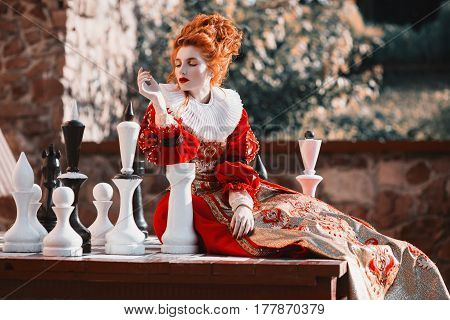 The Red Queen is playing chess. Red-haired woman in a chic vintage dress. Fashion Photo. Chess concept. Make the right choice. Difficult choice