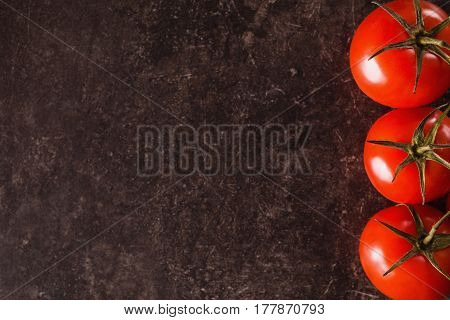 Red cherry tomatoes lie on a dark marble table. Space for text and design. Flat lay cherry copyspace. Cherry tomato in kitchen