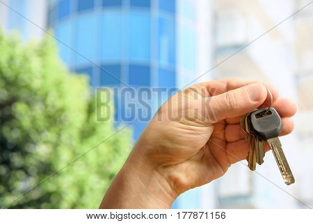 The customer holds the keys to the new apartment against the background of a modern glass building on a sunny day