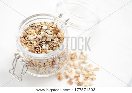 Healthy breakfast of homemade granola cereal nuts and fruit, honey with drizzlier on white background. Morning food, Diet, Detox, Clean Eating, Vegetarian concept.