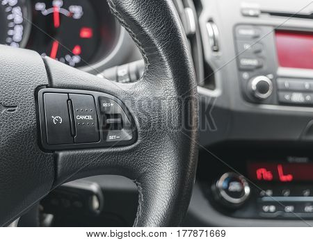 cruise control buttons on the steering wheel of a modern car, car interior details