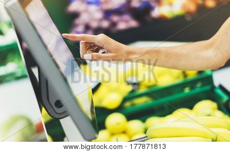 The buyer weighs the yellow bananas and points the fingers on the screen electronic scales woman shopping healthy food in supermarket blur background female hands buy nature products in store grocery