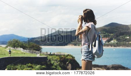 Tourist traveler photographer making pictures sea scape on vintage photo camera on background ocean hipster girl enjoying green peak mountain and nature holiday mock up waves view blurred backdrop