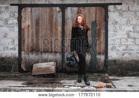 Striking stylish girl with long red hair in black clothes. A stylish woman in a black coat and backpack in hands posing on the background of old wall. Female street fashion style. Beautiful elegant redhead stylish model