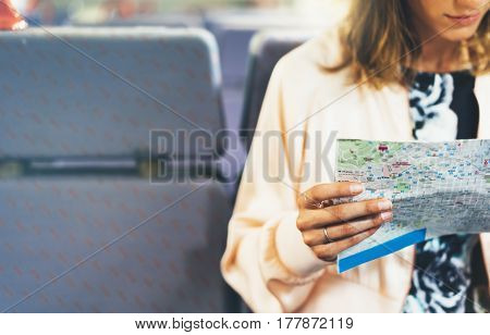 Enjoying travel. Young hipster smile girl with backpack traveling by train sitting near the window holding in hand and looking map. Tourist in summer shirt planing route of railway railroad transport concept