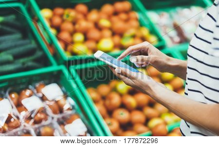 Young woman shopping healthy food in supermarket blur background. Female hands buy nature products using smart phone in store. Hipster at grocery using mobile. Person comparing price of produce poster