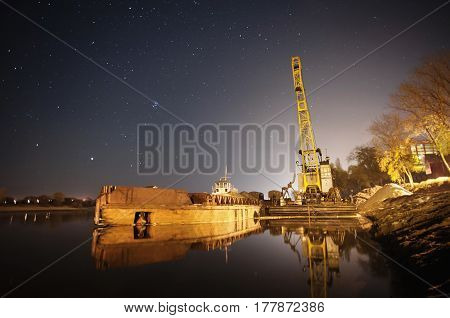The ship is in the water. The beautiful night scenery. Slow shutter speed. Spectacular clear starry sky. Scenic view. The bridge over the river. The port on the river bank. Ship in port