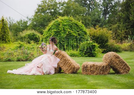 Portrait of a beautiful bride with a bouquet outdoors. Cute lady sits on pressed straw briquettes. Hay bale stack. Pink wedding dress. Grass trees and bushes in the background.